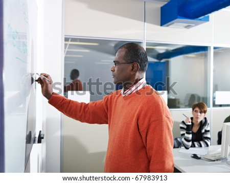 Computer class with indian male teacher writing on board and students in background. Horizontal shape, side view, waist up - stock photo