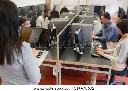 Computer class working as teacher is typing on laptop in college - stock photo