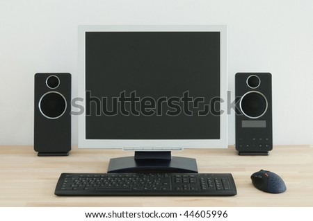 Computer desk with a white wall in the background. - stock photo