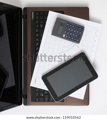 Computer, Digital Tablet, Calculator and Chart on the Desk