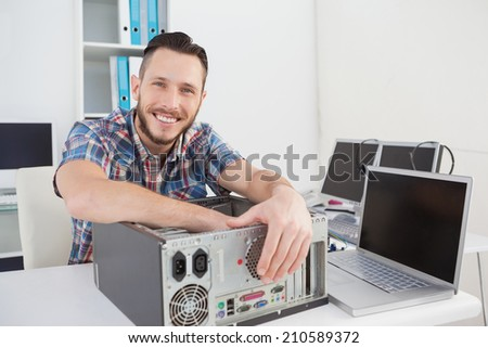 Computer engineer smiling at camera beside open console in his office - stock photo