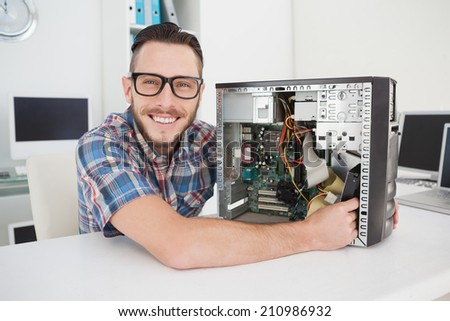 Computer engineer working on broken console smiling at camera in his office - stock photo