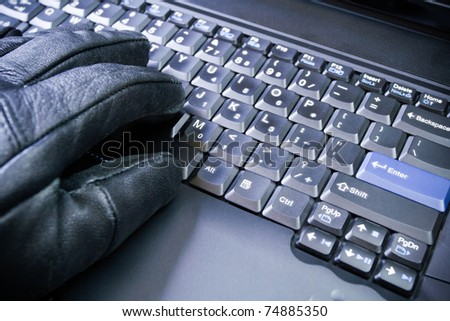 Computer hacker hand in glove working on laptop, dirty business - stock photo