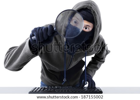 Computer hacker - Male thief stealing data from computer using magnifying glass - stock photo