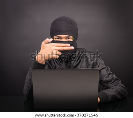 Computer hacker show hand gun - Male thief stealing data from laptop computer on black background