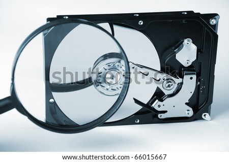 Computer hard disk and magnifying glass. The disc is assembled. - stock photo