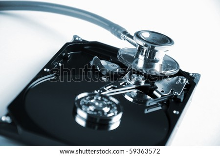 Computer hard drive and a stethoscope. The symbol of health equipment. - stock photo