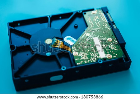 Computer hard drive on blue background (HDD, Winchester). Tilt-shift lens used to accent the center of the hdd and to emphasize the attention its central schemes - stock photo
