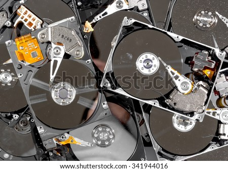 Computer hard drives being recycled. The drives have the tops removed, and are dirty and dusty. The view is from the top. - stock photo
