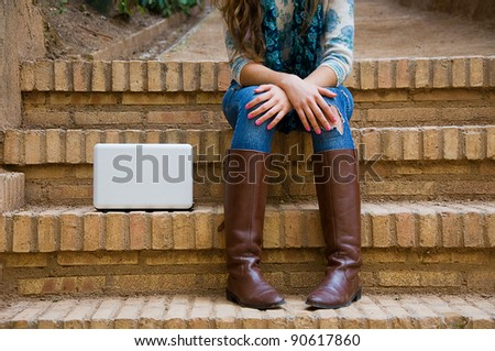 Computer in stairs beside a young girl - stock photo