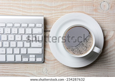 Computer keyboard and cup of hot coffee on a white rustic table. High angle shot in horizontal format. - stock photo