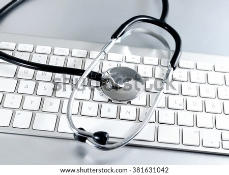 Computer keyboard and stethoscope with selective focus. Image with medical or technical support theme.