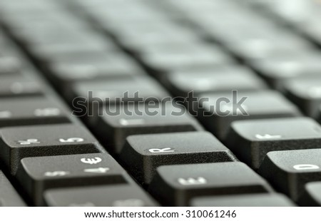 Computer keyboard.  Close up of mostly blurred, light, bands of keys on an angle. - stock photo