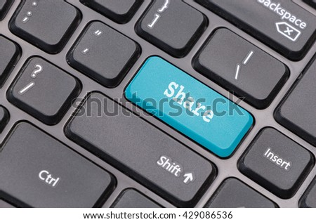 """Computer keyboard closeup with """"Share"""" text on blue enter key - stock photo"""