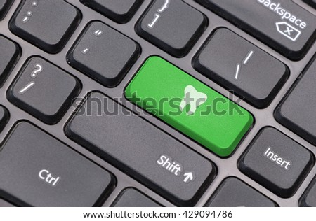 Computer keyboard closeup with tooth icon on green enter key - stock photo
