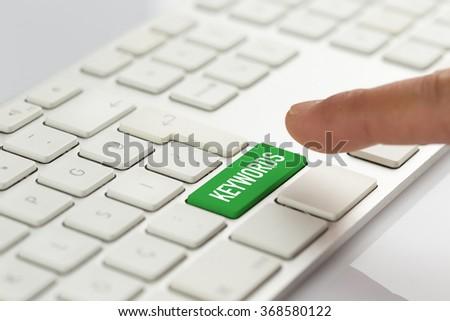 Computer Keyboard Concept: Hand pushing green KEYWORDS keyboard button - stock photo