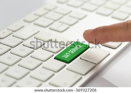 Computer Keyboard Concept: Hand pushing green 24/7 SERVICE keyboard button - stock photo