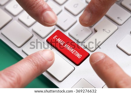 Computer Keyboard Concept: Many fingers pushing red E-MAIL MARKETING keyboard button - stock photo