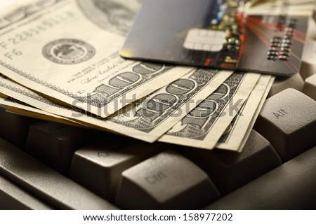 Computer keyboard, credit cards and dollars in cash - stock photo