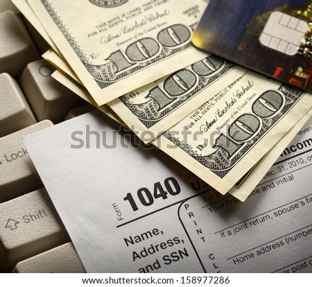 Computer keyboard, credit cards, tax form and dollars in cash
