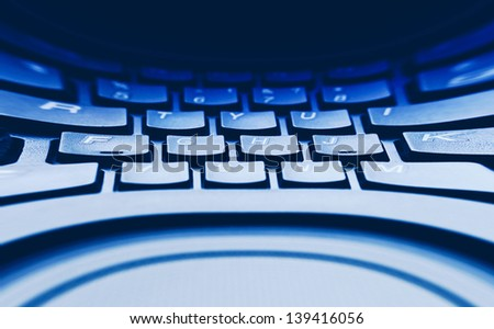 Computer keyboard in blue light. Small depth of field. Pincushion lens use. - stock photo