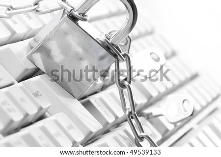 Computer  keyboard secured with chain and padlock - stock photo