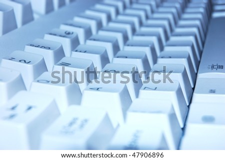 Computer keyboard shot at an oblique angle with a blue tint added - stock photo