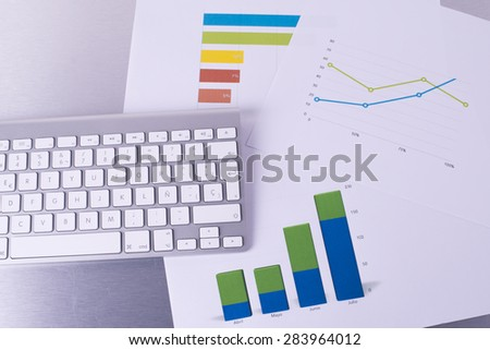 Computer keyboard with graphics papers - stock photo