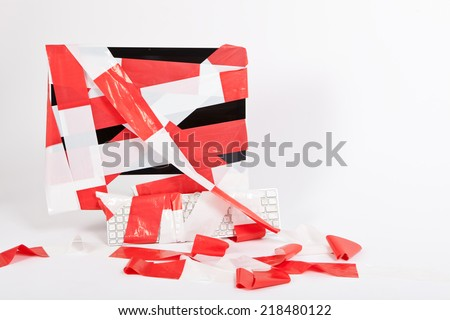 computer monitor and keyboard wrapped in red and white barrier tape, grey background,