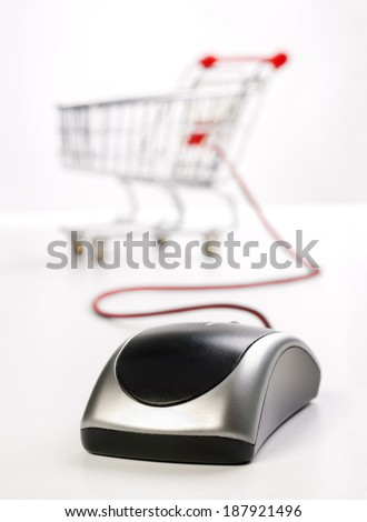 Computer mouse and Cart as a symbol for on-line shopping. - stock photo