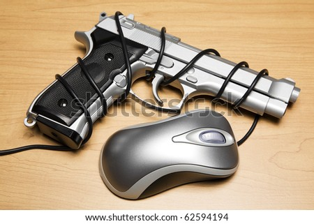 Computer mouse cord tied around a gun - stock photo