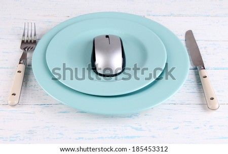 Computer mouse on plate with fork and knife on wooden background - stock photo