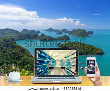 Computer notebook with holding smart mobile on Top view of Ang Thong National Marine Park show Abstract blurred photo of store bokeh background, online shopping concep - stock photo