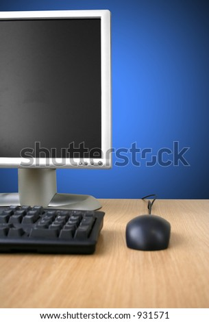 computer on a wooden desk over blue - stock photo