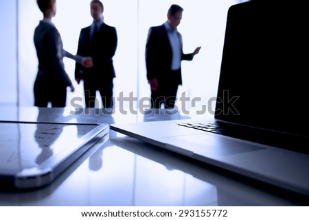Computer on desk , businesspeople standing in the background - stock photo