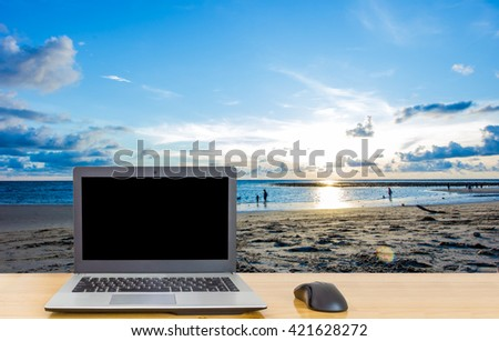 Computer on the table,blur image of the beach at Phuket Island,Thailand on blue tone style as background.