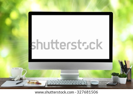 Computer on wooden table on nature green background - stock photo