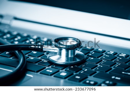 Computer or data analysis - Stethoscope over a laptop computer keyboard toned in blue - stock photo