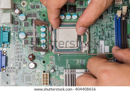 Computer processor installation in CPU socket on the motherboard - stock photo