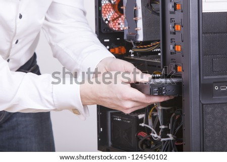 computer support engineer changing the hard drive of an office Computer. Studio shot on a white background.