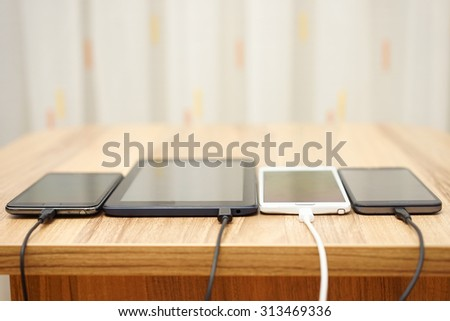 computer tablet and mobile phones charging on home desk - stock photo