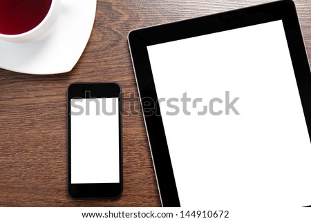 computer tablet and touch phone with isolated screen lie on a wooden table with a cup of coffee - stock photo