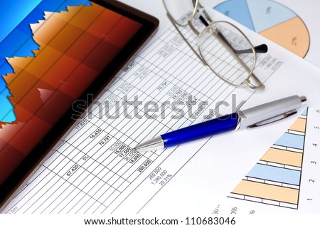 Computer Tablet with Pen Graphs and Spreadsheet of figures - stock photo