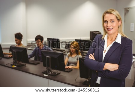 Computer teacher smiling at camera with arms crossed at the university