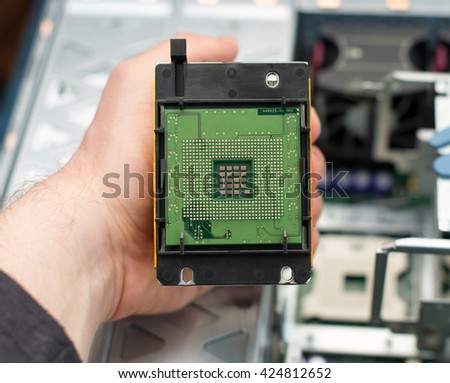 Computer technician holding CPU in front of motherboard.