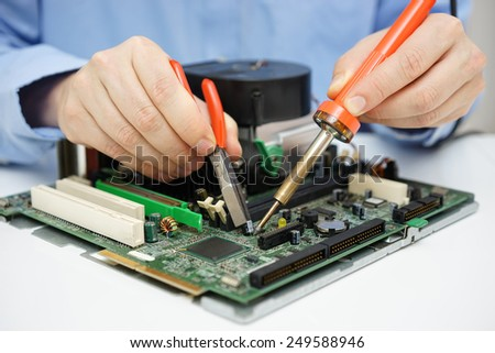 Computer  technician is changing capacitor on faulty motherboard - stock photo