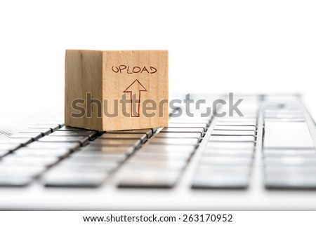 Computer Upload concept with a wooden cube with a hand-drawn arrow and word - Upload - on a white computer keyboard isolated on white with copyspace. - stock photo