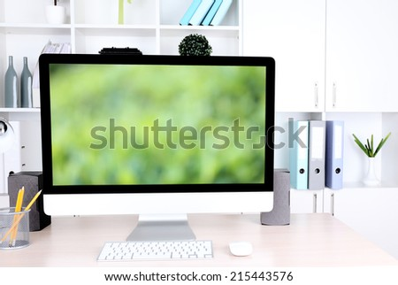 Computer with screensaver on table - stock photo