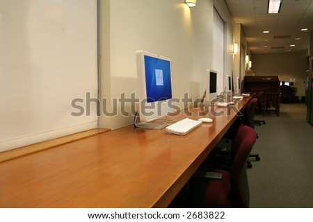 computers lined on a long desk, with one computer turned on - stock photo
