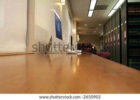 computers lined up on a long desk - stock photo